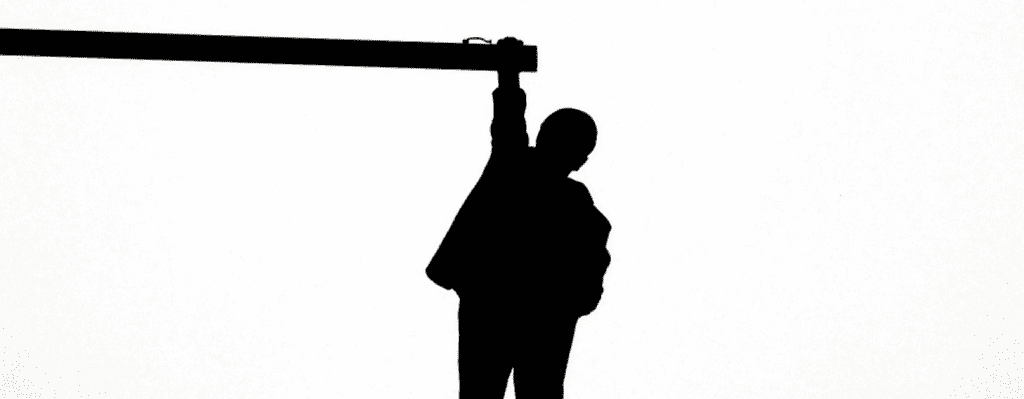 Man dangling from a pole