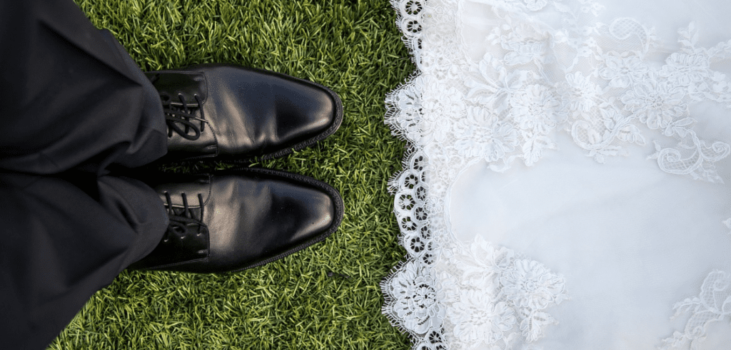 Looking down at a bride's dress and groom's shoes
