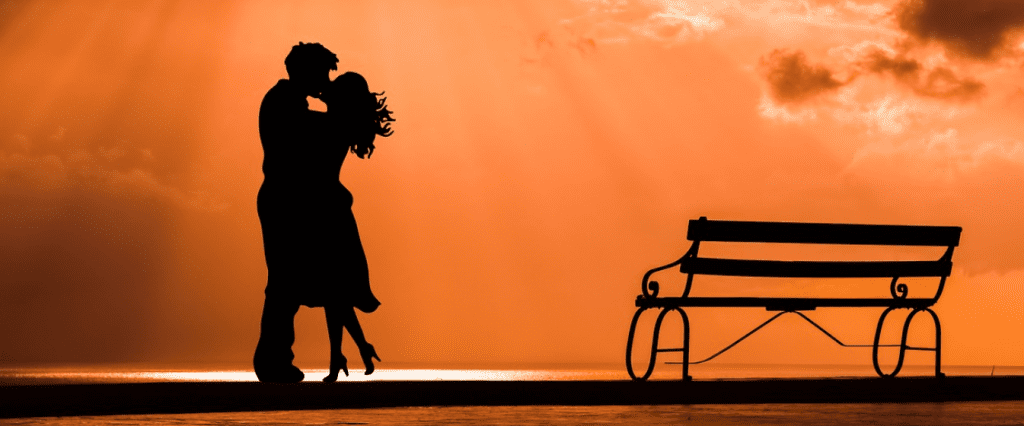 Silhouettes of couple kissing on the beach